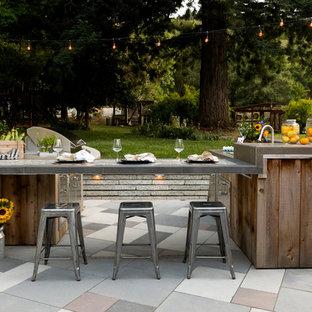 Idee per un patio o portico country dietro casa con pavimentazioni in pietra naturale e nessuna copertura