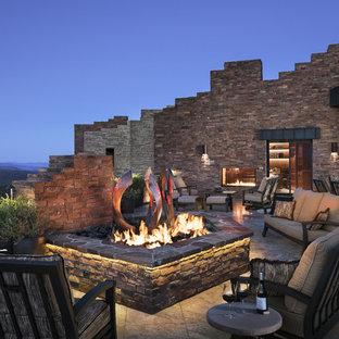 Idee per un ampio patio o portico stile americano dietro casa con un focolare, piastrelle e nessuna copertura