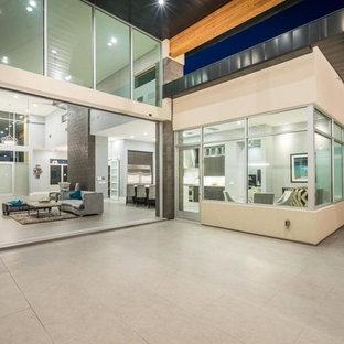 Idee per un ampio patio o portico moderno dietro casa con pavimentazioni in pietra naturale e un parasole