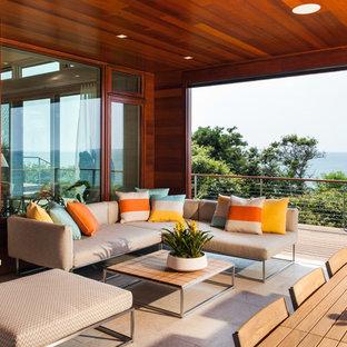 Inspiration för en stor funkis uteplats på baksidan av huset, med takförlängning, en öppen spis och trädäck