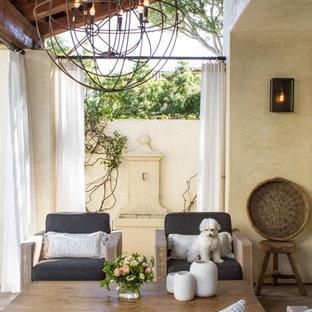 Foto di un grande patio o portico tradizionale dietro casa con fontane, graniglia di granito e un tetto a sbalzo
