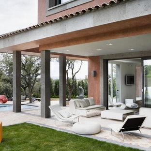Foto di un patio o portico design con fontane, pavimentazioni in pietra naturale e un tetto a sbalzo