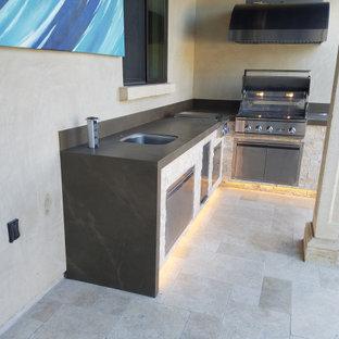 Patio kitchen - large modern backyard patio kitchen idea in Orange County