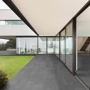 Example of a huge minimalist backyard tile patio design in Miami with a roof extension