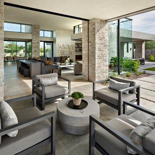 Idee per un ampio patio o portico minimalista dietro casa con piastrelle e un tetto a sbalzo