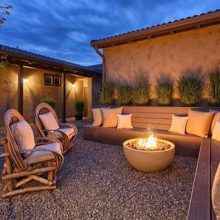 Esempio di un grande patio o portico american style in cortile con un focolare e ghiaia
