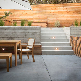 This is an example of a mid-sized modern backyard patio in San Francisco with an outdoor kitchen, concrete slab and no cover.