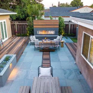 Immagine di un grande patio o portico contemporaneo dietro casa con un caminetto, pedane e nessuna copertura