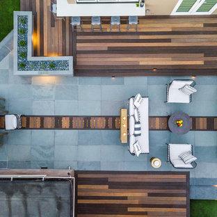 Foto de patio actual, grande, sin cubierta, en patio trasero, con chimenea y adoquines de piedra natural