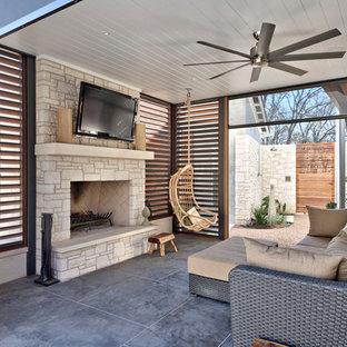 Idee per un ampio patio o portico country con un tetto a sbalzo e un caminetto