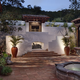 Example of a large courtyard tile patio fountain design in San Diego with a roof extension
