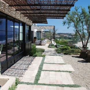 Ispirazione per un ampio patio o portico costiero dietro casa con ghiaia, un focolare e una pergola