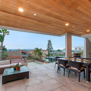 Example of a large minimalist backyard concrete paver patio design in San Diego with a roof extension