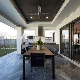 This is an example of a contemporary backyard patio in Sydney with an outdoor kitchen, tile and a roof extension.