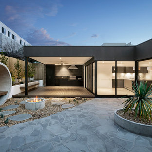 Design ideas for a contemporary patio in Melbourne with a fire feature, natural stone pavers and a roof extension.