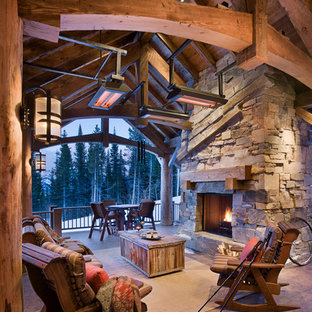 Example of a mountain style patio design in Other with a fire pit and a roof extension