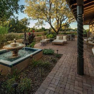 Ispirazione per un patio o portico mediterraneo di medie dimensioni e in cortile con pavimentazioni in mattoni, un tetto a sbalzo e fontane