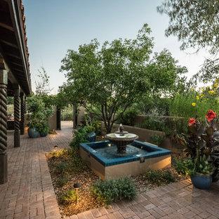 Immagine di un patio o portico mediterraneo di medie dimensioni e in cortile con fontane, pavimentazioni in mattoni e un tetto a sbalzo