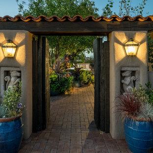 Idee per un patio o portico mediterraneo di medie dimensioni e in cortile con un giardino in vaso, pavimentazioni in mattoni e un tetto a sbalzo