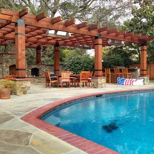 Foto di un grande patio o portico mediterraneo dietro casa con pavimentazioni in pietra naturale e una pergola