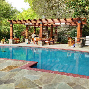 Design ideas for a large mediterranean back patio in San Francisco with an outdoor kitchen, natural stone paving and a pergola.