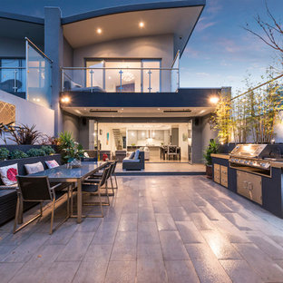 Expansive contemporary courtyard patio in Melbourne with an outdoor kitchen, tile and no cover.