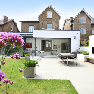 This is an example of a contemporary back patio in London with no cover and a fireplace.