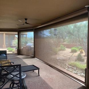 Immagine di un grande patio o portico stile americano dietro casa con pavimentazioni in cemento e un tetto a sbalzo
