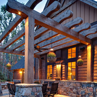 Example of a mountain style stone patio design in Other with a pergola