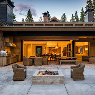 Example of a mountain style backyard concrete patio kitchen design in Sacramento with no cover
