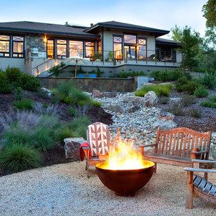 На фото: дворик в современном стиле с местом для костра и покрытием из гравия с