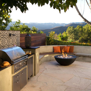 Example of a mid-sized trendy stone patio kitchen design in Los Angeles with no cover