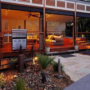 Immagine di un grande patio o portico tradizionale dietro casa con cemento stampato e un tetto a sbalzo