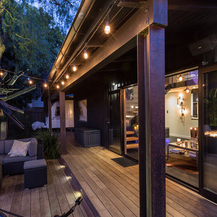 Mid-sized industrial courtyard patio in Auckland with a fire feature, decking and no cover.