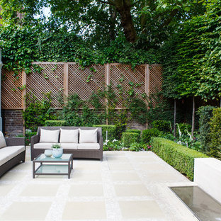 This is an example of a small traditional courtyard patio in London with a water feature and natural stone paving.