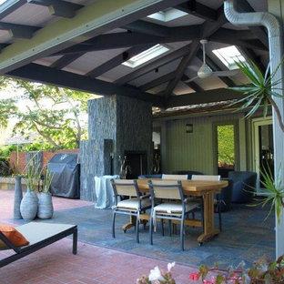 Immagine di un grande patio o portico etnico dietro casa con un focolare, piastrelle e un tetto a sbalzo