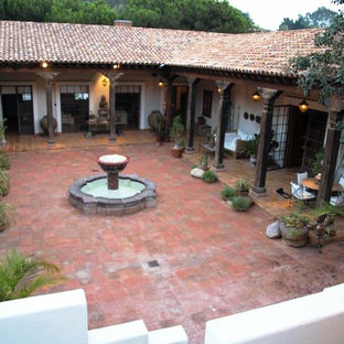 Inspiration for a large courtyard tile patio fountain remodel in San Diego with a roof extension