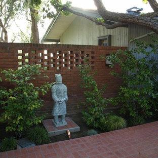 Foto di un grande patio o portico etnico dietro casa con un focolare, piastrelle e un tetto a sbalzo