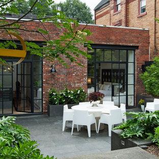Idee per un patio o portico design di medie dimensioni e dietro casa con pavimentazioni in pietra naturale