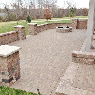 Foto di un grande patio o portico classico dietro casa con un focolare e pavimentazioni in mattoni