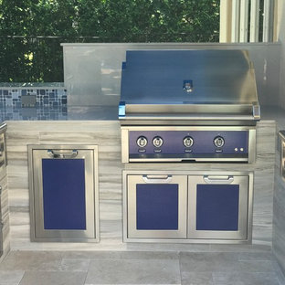 Inspiration for a world-inspired back patio in Miami with an outdoor kitchen, natural stone paving and an awning.