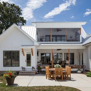 Idee per un patio o portico country di medie dimensioni e dietro casa con pavimentazioni in cemento e un tetto a sbalzo