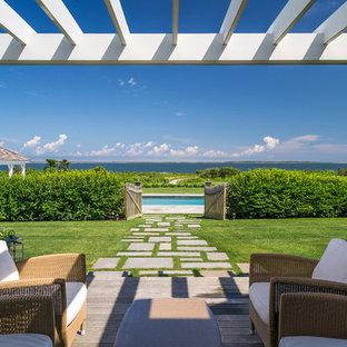 Foto di un ampio patio o portico costiero dietro casa con pedane e una pergola