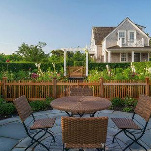 Immagine di un grande patio o portico costiero dietro casa con nessuna copertura e pavimentazioni in pietra naturale