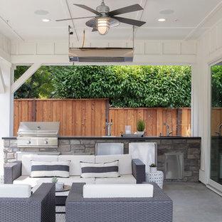 Foto di un patio o portico country di medie dimensioni e dietro casa con lastre di cemento e un gazebo o capanno