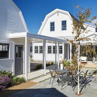Foto på en mellanstor lantlig uteplats på baksidan av huset, med granitkomposit och en pergola