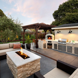 This is an example of a mid-sized traditional side yard patio in San Francisco with an outdoor kitchen and a pergola.