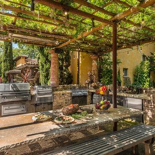 Idéer för en mellanstor rustik uteplats på baksidan av huset, med utekök, grus och en pergola