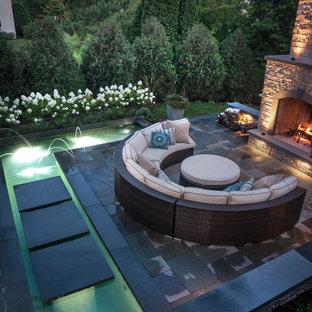 Ispirazione per un patio o portico minimalista di medie dimensioni e dietro casa con fontane e pavimentazioni in pietra naturale