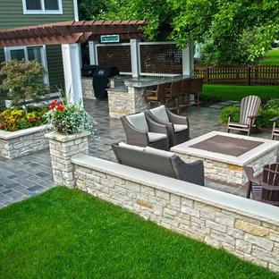 Ispirazione per un grande patio o portico classico dietro casa con un focolare, pavimentazioni in cemento e una pergola